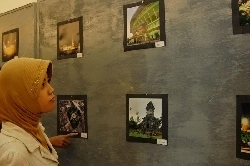Landnmark Malang - Seorang Pengunjung tengah menikmati hasil karya fotografer Kota Malang dalam Kontes Foto bertema Malang Iconique Capture yang di adakan di Hall Malang Olympic Garden (17/02). Pada kontes foto yang bertema landmark Kota Malang, seratusan foto karya puluhan fotografer Kota Malang menampilkan ikon-ikon kota Malang yang dikenal memiliki bangunan yang berniali sejarah tinggi.