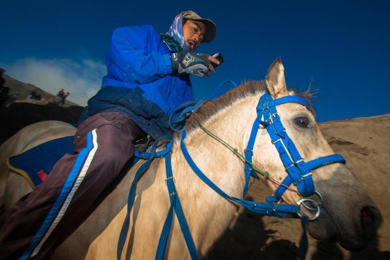 Seorang pemilik kuda di Gunung Bromo mengecek orderan penyewa kuda melalui alat komunikasinya. Perkembangan perangkat komunikasi dari masa ke masa mampu menjangkau daerah yang sangat jauh seperti Gunung Bromo, memudahkan komunikasi, meningkatkan potensi pariwisata dan UMKM.